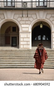 Austin, Texas, United States of America - December 2, 2016: an Asian female Ph.D. graduated wearing hat and gown of the University of Texas at Austin, walking in front of the Main Building