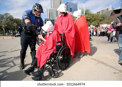 """Austin, Texas / USA - Jan. 20, 2017: An Austin police officer shakes hands with a disabled woman dressed in a """"Handmaids Tale"""" costume at the start of a reproductive rights march to the state Capitol."""