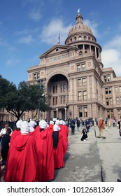 """Austin, Texas / USA - Jan. 20, 2017: Women dressed in """"Handmaids Tale"""" costumes arrive at the Capitol for a rally at the end of a reproductive rights march from city hall."""