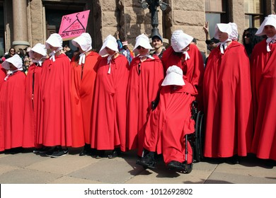 """Austin, Texas / USA - Jan. 20, 2017: Women dressed in """"Handmaids Tale"""" costumes attend a rally for reproductive rights on the steps of the Capitol."""