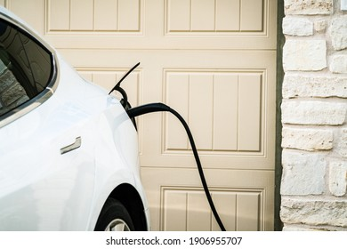 Austin , Texas , USA - January 26th 2020: Tesla Model 3 parked outside suburb neighborhood in Austin Texas plugged in and charging at home