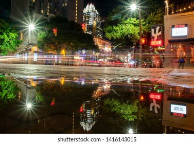 Austin, Texas / USA - June 5, 2019 The view of downtown Austin at night is reflected off of a puddle on 6th Street after significant rainfall.