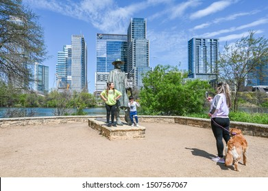 AUSTIN, TEXAS, USA - March 17, 2019: People pose at culpture of Stevie Ray Vaughan at Auditorium Shores in Town Lake Metropolitan Park.  He was a Texas blues guitar legend.
