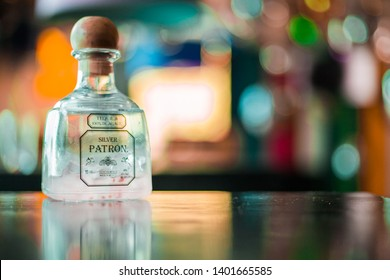 Austin, Texas/ USA- May 17, 2019: Silver patron Tequila bottle/container with pink mixed drink on the bottom with colorful warm background in bokeh