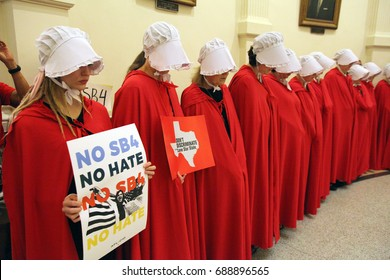 """Austin, Texas, USA - May 29, 2017:  Women wearing """"Handmaid's Tale"""" costumes protest SB 4, an anti-Sanctuary Cities immigration law, under the dome of the state Capitol."""