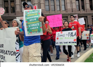 Austin, Texas, USA - May 29, 2017: A teacher and other demonstrators protesting SB 4, an anti-Sanctuary Cities immigration law, march outside the state Capitol.