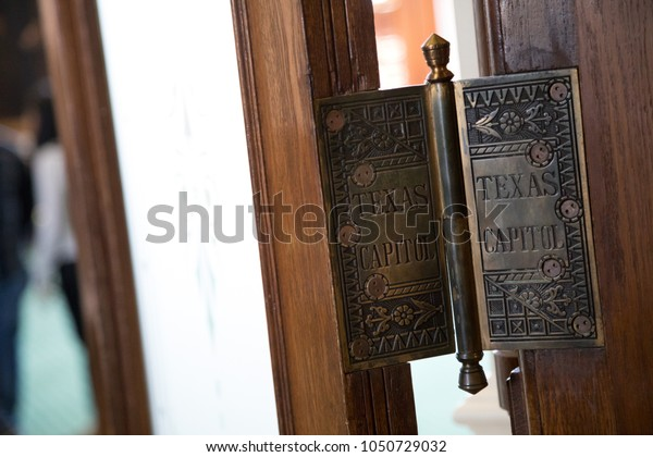 Austin, TEXAS/USA - September 9, 2017: Close up on a brass door hinge, with Texas Capitol engraved, at the State Senate and House of Representatives building