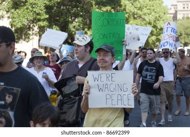 AUSTIN, TX - OCTOBER 15: An unidentified group of protesters carry signs down Congress Avenue during the 'Occupy Austin' march to the Texas State Capitol on October 15, 2011 in Austin.