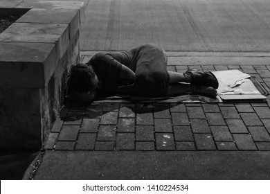 Austin, TX / USA - May 26 2019: homeless woman asleep on cardboard.