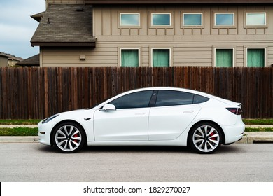 Austin, TX, USA - September 15, 2020 side views of white Tesla Model 3 parked on street in suburb of Austin Texas next to wooden fence