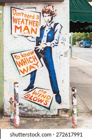 """AUSTIN, TX/USA - APRIL 11, 2015: Mural depicts Bob Dylan's lyrics: """"Don't need a weatherman to know which way the wind blows"""" from the song """"Subterranean Homesick Blues""""; Hole in the Wall Restaurant."""