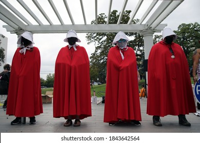 Austin, TX/USA - Oct. 17, 2020: Activists dressed in Handmaid's Tale costumes participate in the Women's March and Rally at a city park.