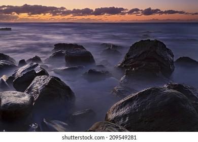 Australia beach rocks wet of surfing waves at sunrise NSW National park