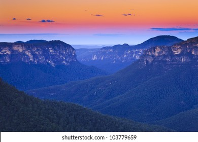 australia blue mountains grand canyon at sunset with colorful sky from yellow via pink to blue eucalyptus forests in valley