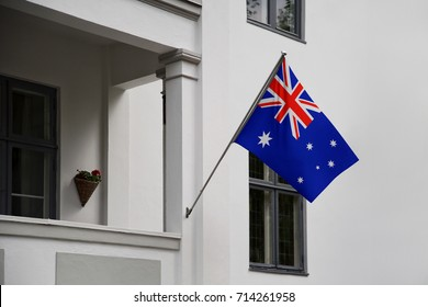 Australia flag. Australian flag displaying on a pole in front of the house. National flag of Australia waving on a home hanging from a pole on a front door of a building.
