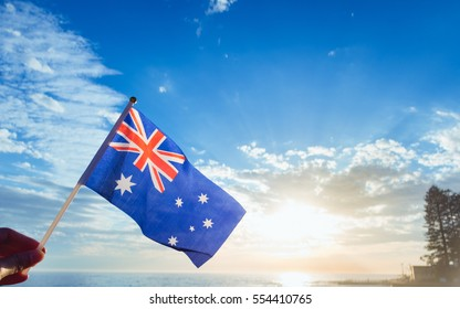 Australia flag national hand hold under blue sky at beach with sunlight