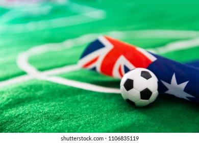 Australia flag and soccer ball on green grass field