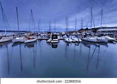 Australia Hobart city marina docked at sea and river cove at sunset panoramic view on yachts with masts reflecting in still water