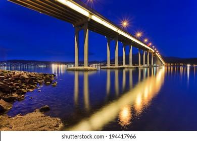 Australia Hobart Tasman bridge side view at sunrise illuminated columns and reflection in still water of Derwent river