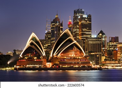 Australia iconic SYdney city landmarks CBD harbour and famous buildings greatly illuminated at sunset with reflection in still blurred harbour waters backgrounded by high-rises