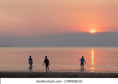 Australia; Jun 2020: Kids playing at the beach at sunset time. Red and orange sky. Three young friends at the shore with feet in the ocean. Darwin, Northern Territory NT, Australia