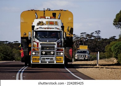 AUSTRALIA - MAY 20: Pilot car following a huge Australian truck to close the convoy while another above the truck on an Australian road, may 20, 2007.