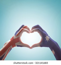 Australia national flag  on people hands in heart shape isolated on sky background for labour day and national Anzac holiday celebration