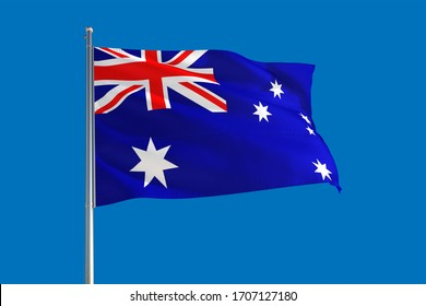 Australia national flag waving in the wind on a deep blue sky. High quality fabric. International relations concept.
