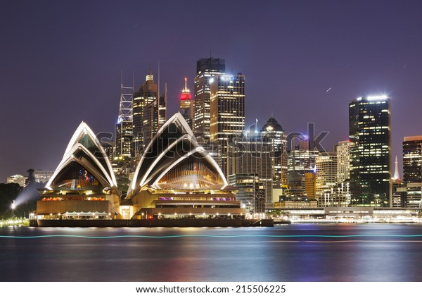 Australia SYdney City CBD close up view over harbour waters at sunset dark sky and reflections of city lights in blurred water
