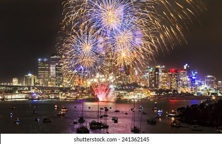 Australia Sydney city highlighted at New Year celebration fireworks with colourful fire balls above skyscrapers and harbour