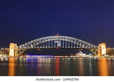 AUstralia sydney harbour bridge side view on iconic landmark at sunset with bright illumination and star tracks