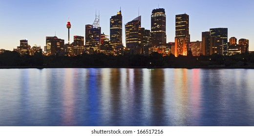 australia sydney panoramic view on city CBD skyscrapers and office towers over harbour with illuminated lights reflected in still water at sunset