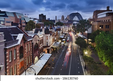 australia sydney the rocks historic district in the city view from top on george street illuminated houses and Sydney Bridge in the background at sunset