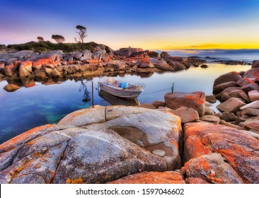 Australia Tasmania bay of fires Binalong coast and small lagoon bay wiht fishing boat anchored at sunrise between red bacteria-covered rocks.