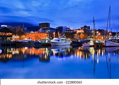 Australia Tasmania Hobart sullivan's cove at sunset illuminated buildings gallery and docked yachts with lights