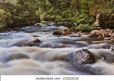 australia Tasmania St Clair lake national park watersmeet point water rivers meet blurred current over stones and boulders with aboriginal stone sign