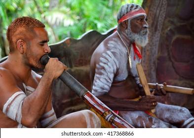 Australian Aboriginal men play Aboriginal music on didgeridoo and wooden instrument during Aboriginal culture show in Queensland, Australia.