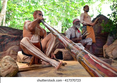 Australian Aboriginal men play Aboriginal music on didgeridoo and wooden instrument during Aboriginal culture show in Queensland, Australia.