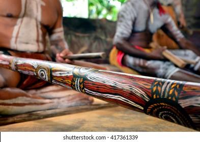 Australian Aboriginal men playing  Aboriginal music on didgeridoo and wooden instrument during Aboriginal culture show in Queensland, Australia.