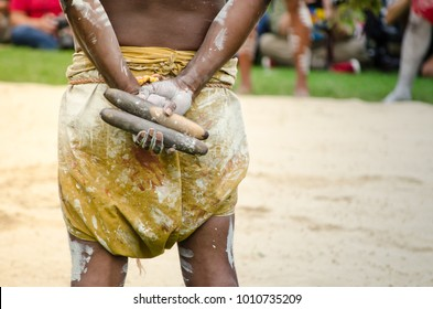 Australian aboriginal people holding Traditional Wood Claves percussion instruments.