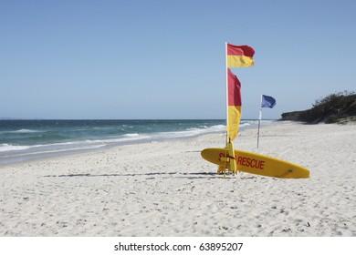 Australian Beach Surf Rescue surfboard and flags on Bribie Island beach, Queensland, Australia