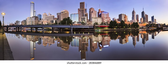 Australian capital city Melbourne at sunrise. Still reflection of city CBD in Yarra river waters in panoramic format