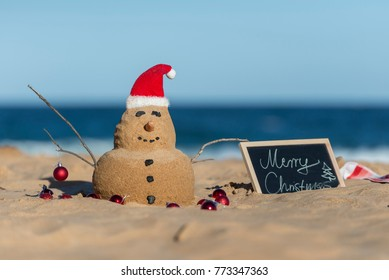 Australian Christmas Sandman with decoration and with a board of Merry Christmas text on the iconic Bondi Beach in Sydney