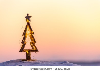 An Australian Christmas, a simple tree decorated with fairy lights on the beach in summer with warm light.  Space for message
