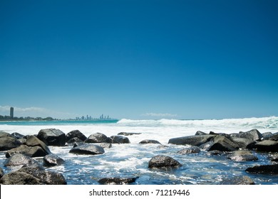 australian coast during the day with rocks in foreground (burleigh heads,qld)