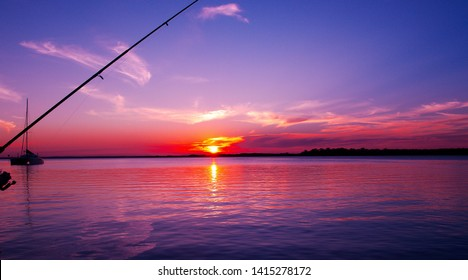 Australian colourful red pink cirrus cloudy sunset seascape with a bright blue sky and sparkling sea water reflections. A vibrant nautical nature background image. Sydney Harbour, New South Wales