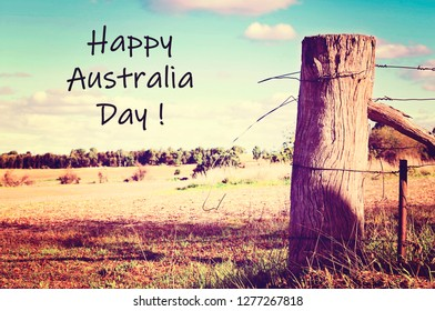 Australian country side scene with old gate post and barb wire, with applied vintage wash filter, and Happy Australia Day text greeting.