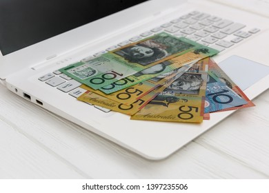 Australian dollar banknotes on white laptop keyboard