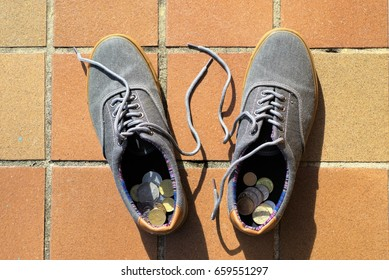 Australian dollar coins inside canvass shoes
