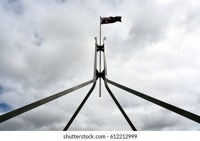 The Australian flag flying on top of Parliament House with cloudy sky. Flag flies on giant flagpole over Parliament House in Canberra, the seat of government in Australia.